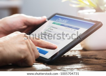 Close-up Of A Businessperson's Hand Filling Checklist Form On Digital Tablet