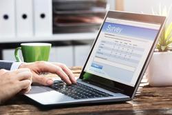 Close-up Of A Businessperson's Hand Filling Online Survey Form On Laptop Over Wooden Desk