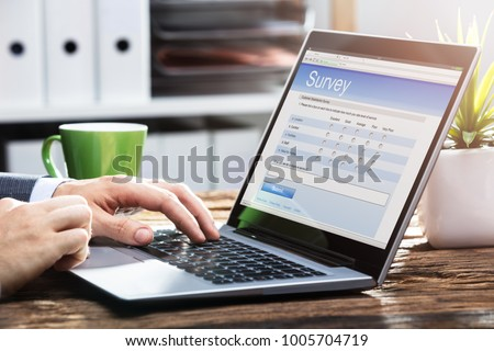 Close-up Of A Businessperson's Hand Filling Online Survey Form On Laptop Over Wooden Desk #1005704719