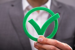 Close-up Of A Businessperson's Hand Holding Green Check Mark Icon