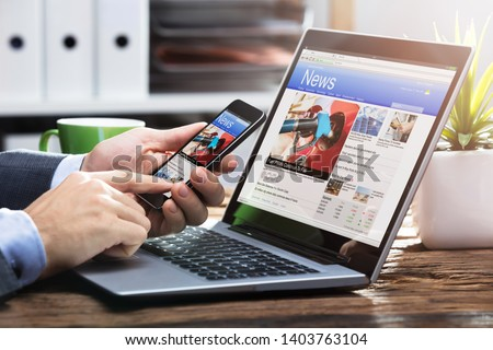 Close-up Of A Businessperson's Hand Holding Mobile Phone With Online News On Screen