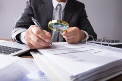 Close-up Of A Businessperson's Hand Looking At Receipts Through Magnifying Glass At Workplace
