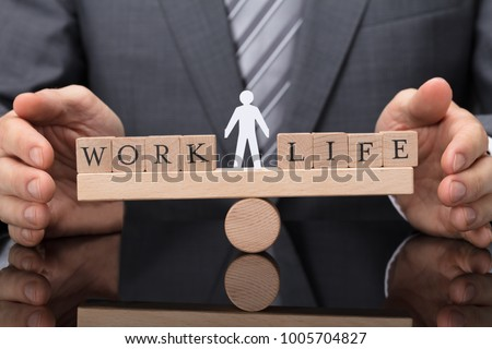 Close-up Of A Businessperson's Hand Protecting Balance Between Life And Work On Wooden Seesaw