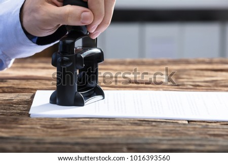 Close-up Of A Businessperson's Hand Stamping With Approved Stamp On Document #1016393560