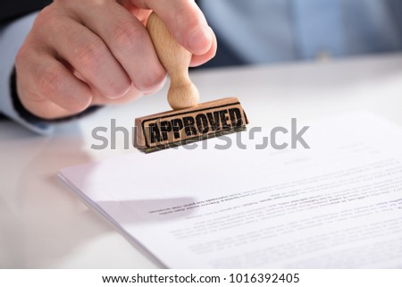 Close-up Of A Businessperson's Hand Using Stamper On Document With Approved Text