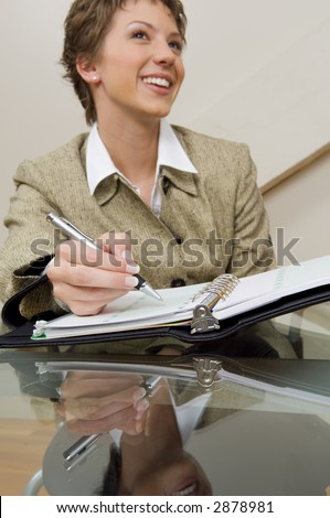 Close-up of a businesswoman at a glass desk with a planner.