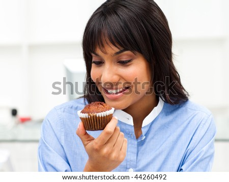 Close-up of a businesswoman eating a muffin at her desk - stock photo