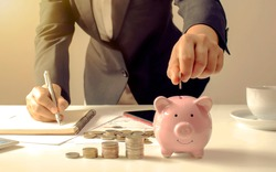 Close-up of a businesswoman holding a coin in a piggy bank, a concept of saving money for financial accounting.