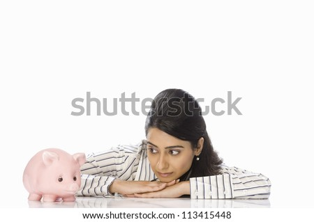 Close-up of a businesswoman looking at a piggy bank