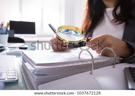 Close-up Of A Businesswoman's Hand Checking Bill Through Magnifying Glass At Workplace