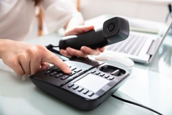 Close-up Of A Businesswoman's Hand Dialing Telephone Number To Make Phone Call In Office