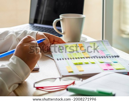 Close-up Of a businesswoman's hands organizing agenda with sticky notes at the workplace. Color planning for productivity and remainder of important appointments. Desk with coffee cup, laptop and glas Stock fotó ©
