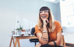 Close up of a businesswoman sitting in office and laughing resting her chin on her hand. Smiling woman entrepreneur wearing eyeglasses taking a break from work.