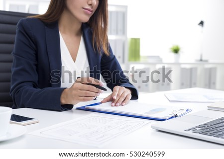 Close up of a businesswoman with tanned skin holding a pen and sitting at her table with a clipboard.