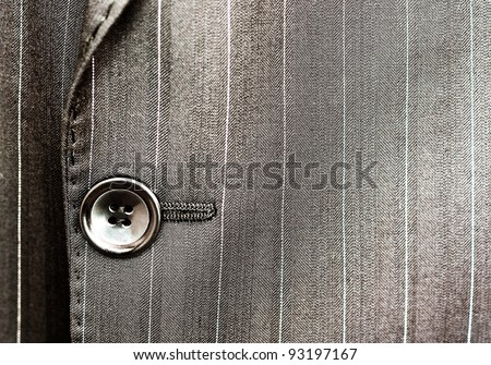 Close up of a button on a pin striped business suit coat