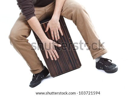 Close-up of a cajon, man's legs and hands are shown as he's playing the instrument - isolated on white