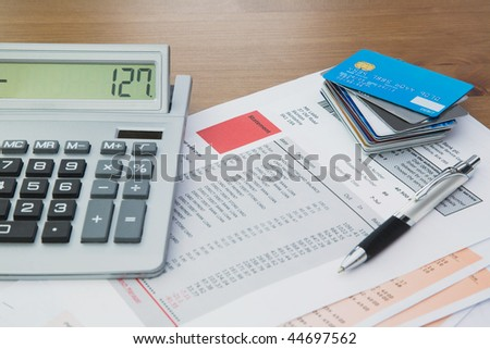 Close up of a calculator with bank and credit card statements and a pile of credit cards on top of the statements,