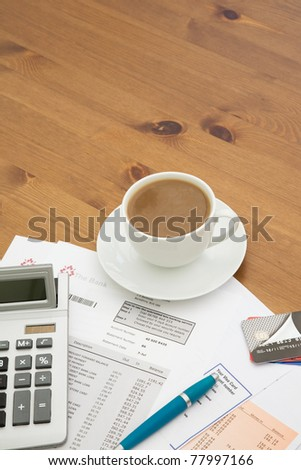 Close up of a calculator with bank and credit card statements and a pile of credit cards with a cup of hot coffee