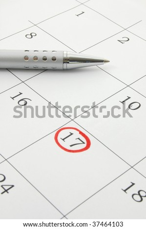 close up of a calendar page, with pen and notice - stock photo