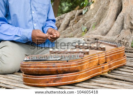 Close-up of a Cambodian musician playing a traditional khim musical instrument. A hammered dulcimer, or zither, style of instrument it has brass strings struck with bamboo hammers.