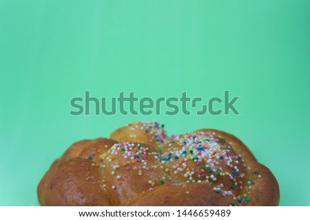 Close-up of a candy with colorful decoration on a green background where there is space to write texts or add graphics. Copy Text #1446659489