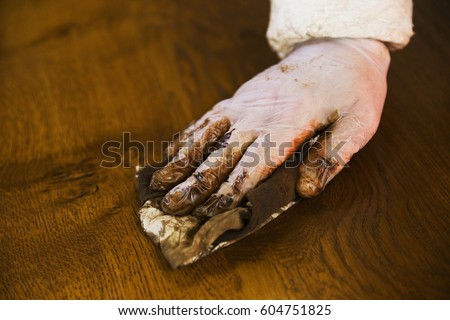 Close up of a carpenter wearing protective gloves, applying varnish onto a wooden surface with a cloth #604751825