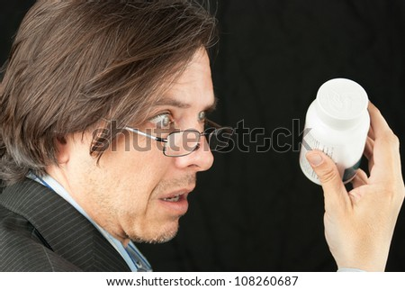 Close-up of a casual businessman looking over glasses trying to read a pill bottle label.