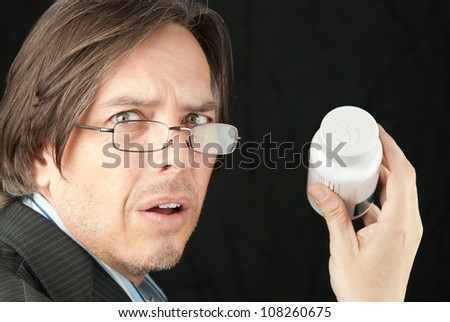 Close-up of a casual businessman wearing glasses frustrated trying to read a pill bottle label.