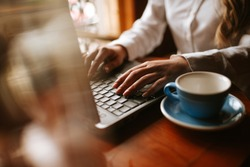 Close up of  a caucasian  girl typing on a keyboard lap top next to a cup of coffee