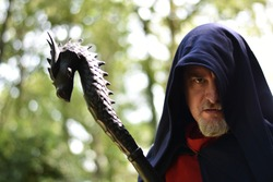 Close-up of a caucasian man over 40 wearing an hooded cloak and holding a black wooden  staff topped by a dragon head. The hood hides his left eye, could be a wizard or even  Odin in disguise.