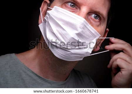 Close up of a caucasian man putting on a medical face mask with one hand stretching the elastic band and putting the protective mouthpiece on