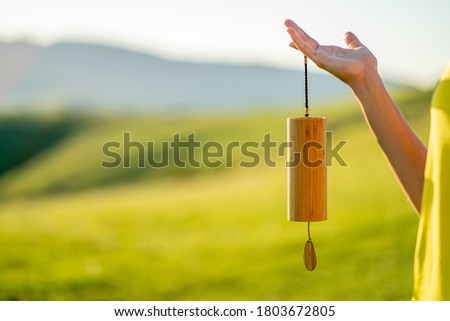 Close-up of a Caucasian woman hand holding a Koshi chime musical instrument against a green background, enjoying the beautiful and relaxing sounds on a sunny day in the heart of nature. Copy space. Stock photo ©