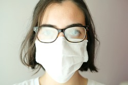 Close up of a caucasian woman wearing a white face mask during coronavirus outbreak with her glasses foggy from breath; mask problems