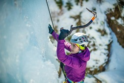 Close up of a Caucasian woman with ice climbing equipment, hiking at a frozen waterfall, swinging the ice axe