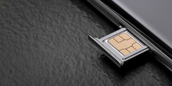 Close up of a cell phone with sim card on dark background. Panoramic image with copy space.