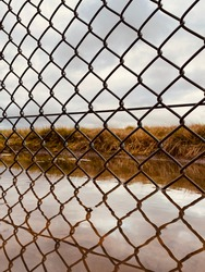 Close up of a chainlink fence with reflection on the below water with grassland behind it.