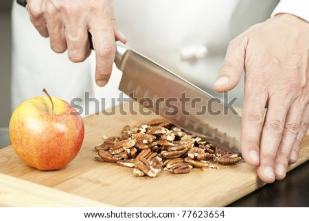 Close-up of a chef chopping pecans.