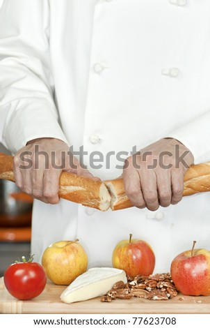 Close-up of a chef holding a baguette in front of a bamboo cutting board of apples, brie and pecans.