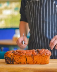 Close-up of a chef holding bread, cutting bread. Professional chef cook cut loaf of bread outside. Restaurant concept. Fresh bakery.