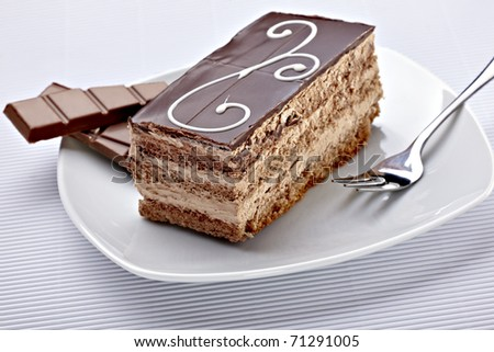 close up of a chocolate cream cake on white plate