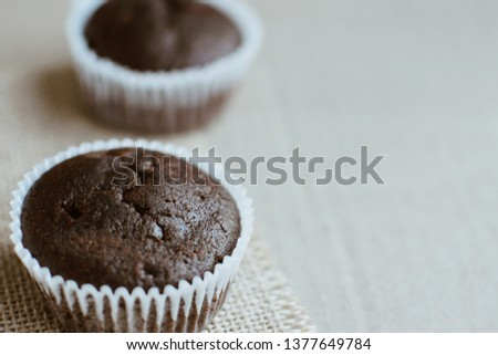 Close up of a chocolate muffin against a textured background. Baked cupcakes. Plenty of Copy space. #1377649784