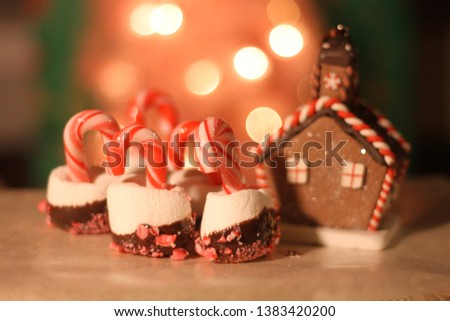 Close up of a Christmas treat of a marshmallow coated in chocolate and crushed candy cane with a candy cane in the center. Bokeh lights illuminate the background with a blurred gingerbread house.