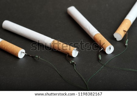 close-up of a cigarette with an orange filter lying on a dark background to the cigarette filters are hooked fishing hooks with thread #1198382167