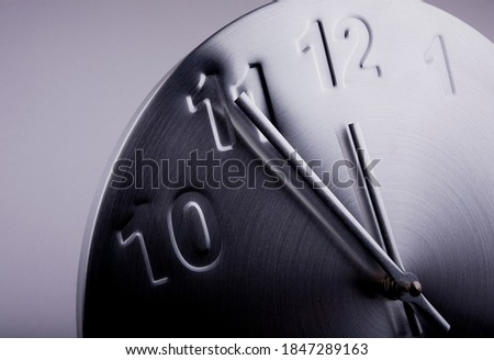 Close up of a clock showing five minutes to twelve. Counting down to midnight. stock photo