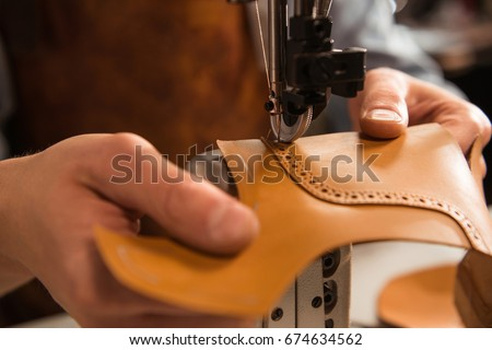 Close up of a cobbler stitching a part of the shoe at a workshop