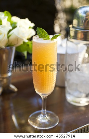 Close-up of a cocktail on a counter, with a bouquet of white flowers in the background. Vertical format.