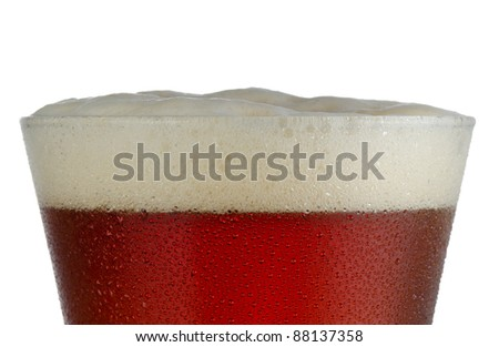 Close up of a cold frosted pilsner beer glass with dark ale and head just above rim level