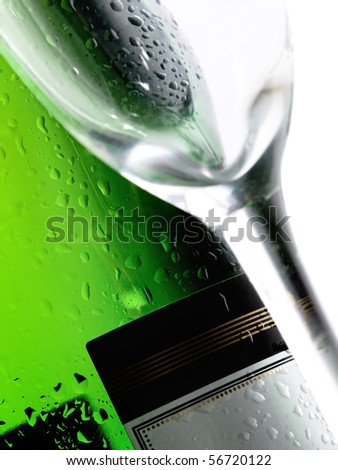 Close-up of a cold wet bottle of alcoholic drink with glass(focus on bottle)