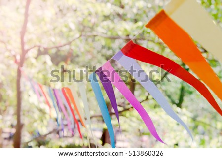 Close up of a colorful party banner tied between trees in a park at an open-air celebration event. #513860326