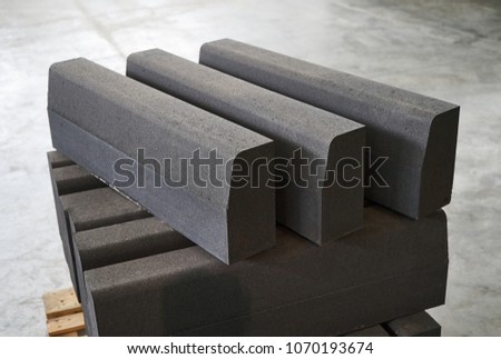 Close-up of a Concrete road curbs at the factory for the production of cement products, paving slabs, construction material for a new sidewalk